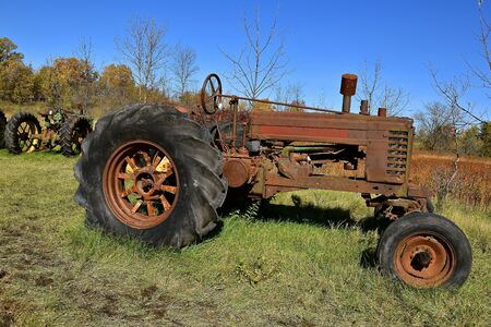 An old rusty tractor with oversized tires is parked in a field.
