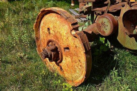 The rusty wheel without a tire belongs to an old tractor. Stock Photo