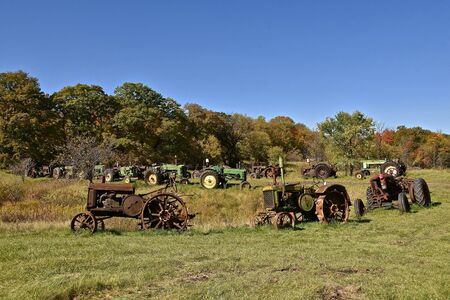 VERGAS, MINNESOTA, October 6, 2019: A row of very old John Deere tractors lined up in a rural setting are products of John Deere Co, an American corporation that manufactures agricultural and construction equipment, drive trains, and transmission