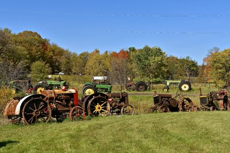 VERGAS, MINNESOTA, October 6, 2019: A row of very old John Deere tractors are lined up against autumn leaves are product sof John Deere Co, an American corporation that manufactures agricultural and construction equipment, drive trains, and transmission