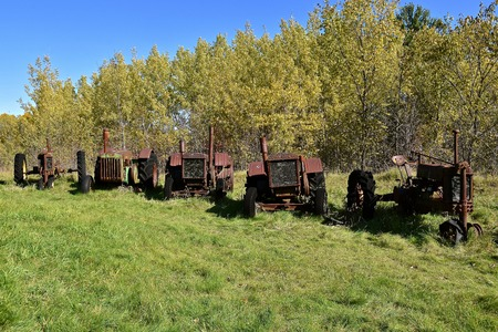 VERGAS, MINNESOTA, October 6, 2019: A row of very old John Deere tractor s are lined up against autumn leaves are  product sof John Deere Co, an American corporation that manufactures agricultural and construction equipment, drive trains, and transmission Editorial