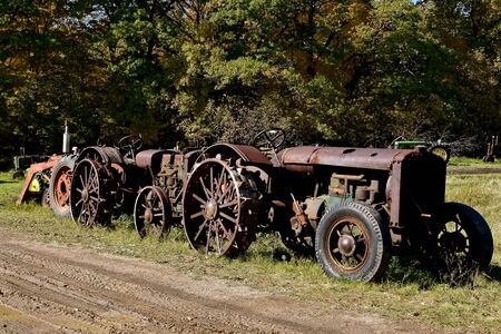 A  muddy rural  gravel road is lined with a row of old rusty tractors.