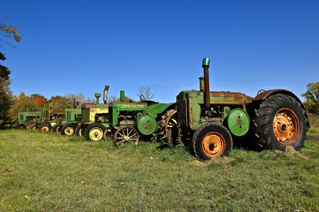 VERGAS, MINNESOTA, October 6, 2019: A row of very old John Deere tractors lined up in a rural setting are products of John Deere Co, an American corporation that manufactures agricultural and construction equipment, drive trains, and transmission Imagens