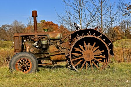 An old unidentifiable rusty tractor is left in a wooded area.