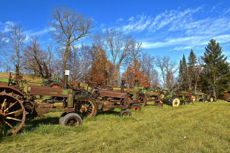 VERGAS, MINNESOTA, October 6, 2019: Very old John Deere tractors are lined up against autumn leaves are products of John Deere Co, an American corporation that manufactures agricultural and construction equipment, drive trains, and transmission