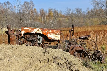 The remains of an old rusty tractor are partially hidden behind a pile of clay soil. Stock Photo