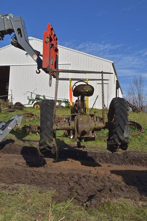 VERGAS, MINNESOTA, October 6, 2019: An old  John Deere tractor being hoisted by a lift fork is a product of John Deere Co, an American corporation that manufactures agricultural and construction equipment, drive trains, and transmissions