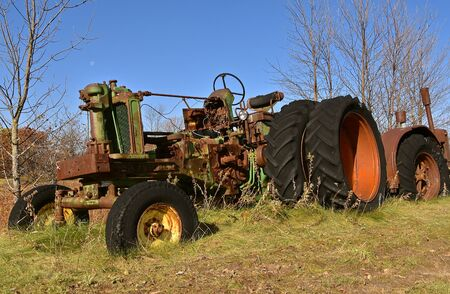 VERGAS, MINNESOTA, October 17, 2019: The junked old John Deere tractor is a product of John Deere Co, an American corporation that manufactures agricultural and construction equipment, drive trains, and transmission