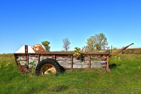 A rusty manure spreader with a wooden box  missing the beater is left parked in the long grass.