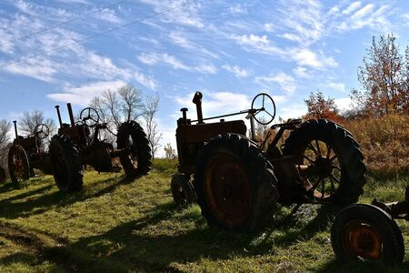 Unidentifiable old tractors are silhouetted against the sky and hill in the autumn season