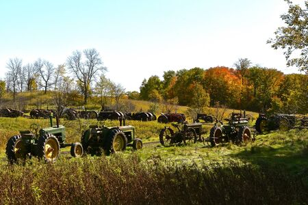 VERGAS, MINNESOTA, October 6, 2019: A row of very old John Deere tractors lined up in a pasture are products of John Deere Co, an American corporation that manufactures agricultural and construction equipment, drive trains, and transmission Editorial