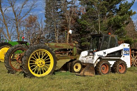 VERGAS, MINNESOTA, October 17,  2019: The 763 Bobcat skid steer pushing an old tractor is headquartered in West Fargo, North Dakota.