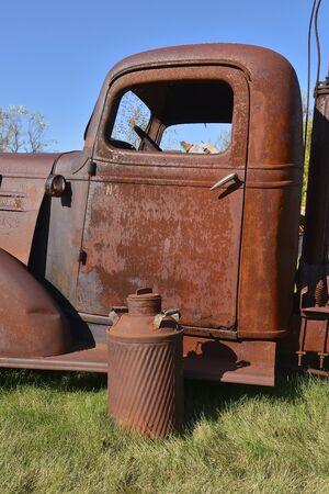 A rusty old milk can is in front of a rust covered truck door.