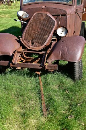 The rusty dilapidated remains of an old truck with a missing grill has an extended front tow bar.