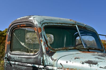 The cab of an old pickup displays a cracked windshield, rust and layers of patina
