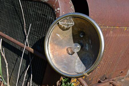 A broken front glass headlight of an old rusty car has the bulb still intact.