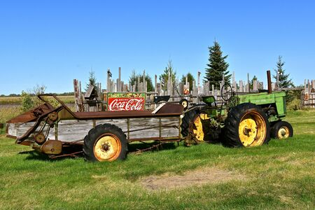 DOWNER, MINNESOTA, October 6, 20119:  T 2015: The old John Deere tractor pulling a manure spreader is a product of John Deere Co, an American corporation that manufactures agricultural, construction, forestry machinery, diesel engines, and drive trains