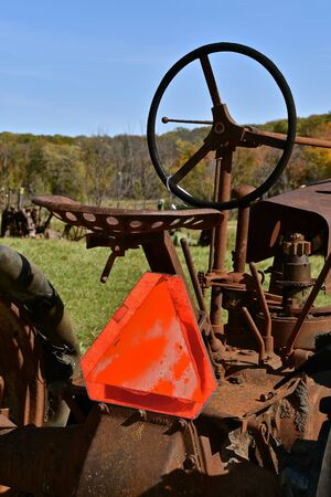 An old rusty tractor has an attached Slow Moving Vehicle Sign providing safety.