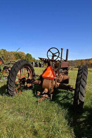 VERGAS, MINNESOTA, October 6, 2019: The parked old tractor with a SMV orange sign is a product of John Deere Co, an American corporation that manufactures agricultural and construction equipment. Imagens