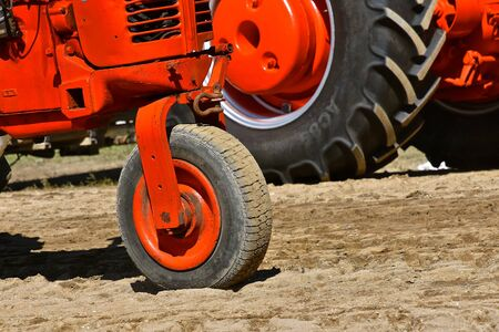 A restored orange tractor has only one front wheel.