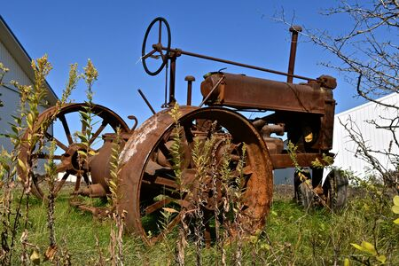 An old unidentifiable rusty tractor with lug wheels is left isolated in the weeds