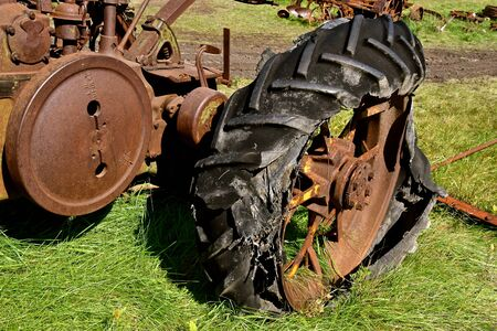 An old unidentifiable rusty tractor with a rotten and disintegrated tire is left in a salvage and junkyard. 스톡 콘텐츠
