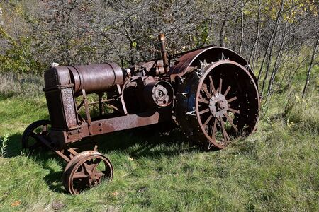 An old unidentifiable rusty tractor with lug wheels is left isolated in a woods