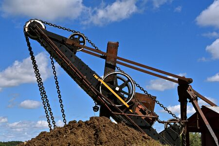 A steam powered excavating machine scoops a load of earthen material in the huge bucket driven by chains and gears.