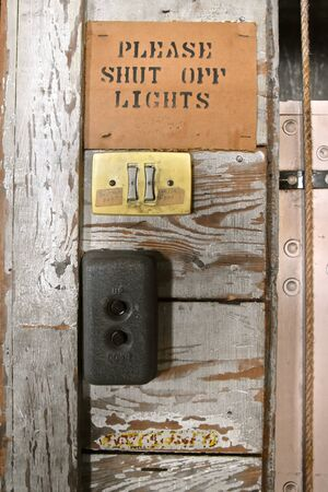 The sign, push button switch, and directions of an old wooden warehouse lift elevator.