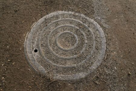 A steel man hole cover for a sanitary sewer system is located on a gravel road. Foto de archivo