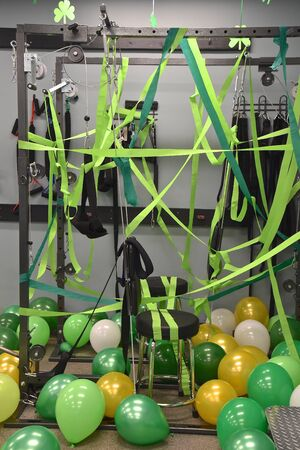 The exercise equipment  of a chiropractor is decorated with green balloons and ribbon in celebration of St. Patrick's Day