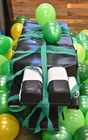 The treatment bed(bench) of a chiropractor is decorated with green balloons and ribbon in celebration of St. Patrick's Day