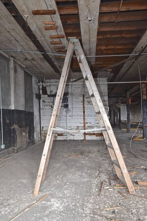 A rickety old wooden stepladder is being used to reach the ceiling of a renovation project of an old warehouse.