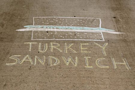 A chalk drawing on a driveway display a split sandwich with turkey slices as the filler.