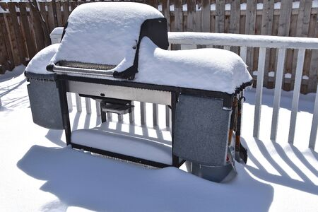 An outdoor grill situated on a patio throws it's shadow after a snowfall. Banque d'images