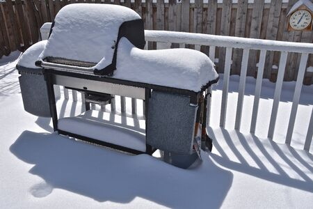 An outdoor grill situated on a patio throws it's shadow after a snowfall with a thermometer on the back fence. Banque d'images