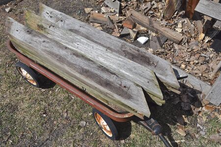 The retro red wagon loaded with old wood  is a Radio Flyer product which also makes tricycles, bicycles, and ride-ons and is base in Chicago, IL where it was founded in 1917 Banque d'images
