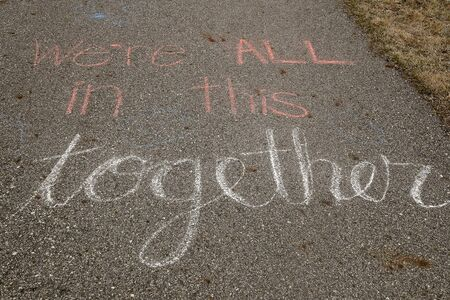 A sidewalk art message encourages togetherness during the Covid-19 pandemic. Banque d'images