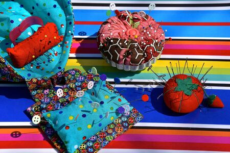 An array of pin cushion arranged on a colorful material