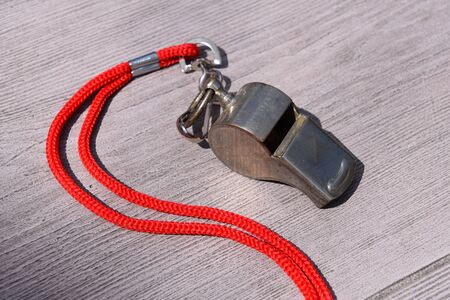 An old metal whistle with an attached lanyard is ready for usage.