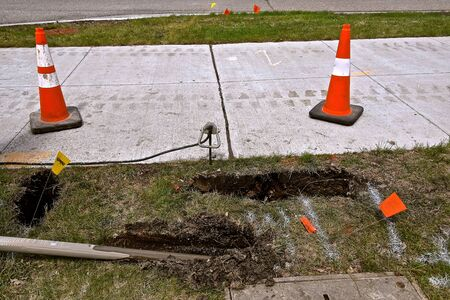 Drilling pipe for burying optic telecommunication cable underground alongside a sidewalk with orange warning cones