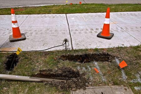Tube de forage pour enterrer le câble de télécommunication optique sous terre le long d'un trottoir avec des cônes d'avertissement orange