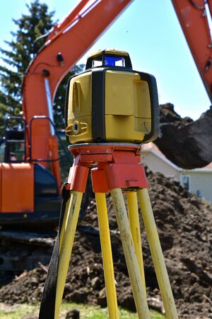 A surveyor's equipment, tacheometer or theodolites being used at a construction site with an excavator in the background. Imagens