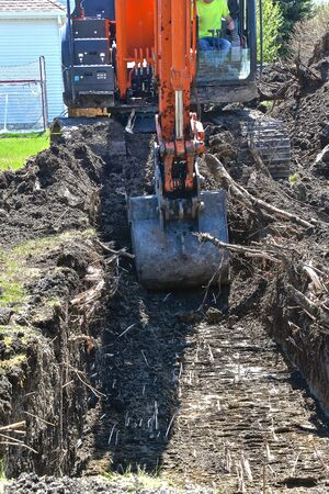 A trench is being dug  by an excavating machinefor the footings of a new garage site. 스톡 콘텐츠