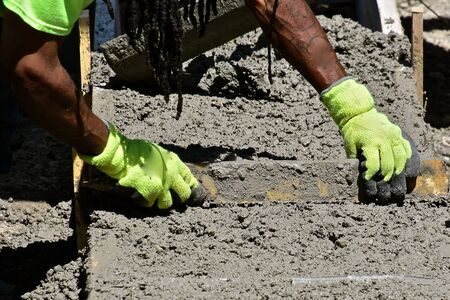 A concrete  worker levels fresh mud in the creation of a new foundation for a building