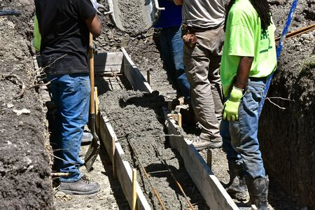 Unidentified workers move wet concrete