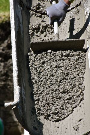 Wet concrete pours down a chute from a ready-mix truck at a building site. 스톡 콘텐츠
