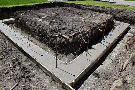 Forms are in place to receive concrete in creating a foundation at a building site with anchor rods throwing their shadows.