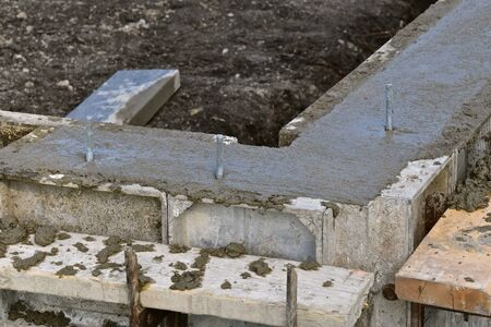 The corner of a forms where fresh mud(concrete has been poured, troweled, and secured with anchor rods.  process