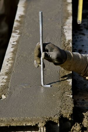 An anchor rod is in the process of being submerged into the wet concrete of a newly formed foundation.